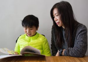 Lam's son is reading his Chinese Language textbook in Putonghua.