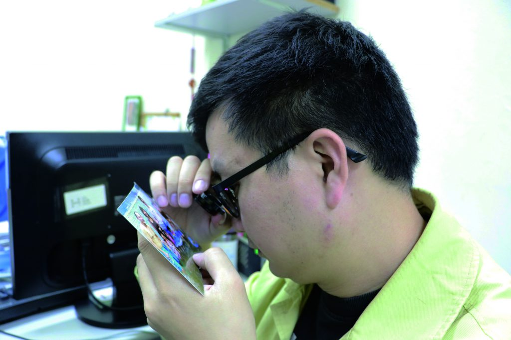Galant Ng Ka-lun uses a magnifying glass to read.