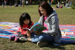 A parent and child reading together at a picture books and music festival.